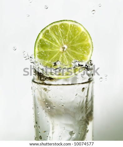 Lime slice falling in a glass of water - stock photo