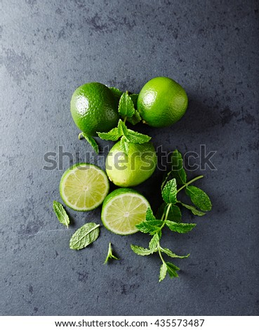 Limes and Fresh Mint Leaves on a Black Stone - stock photo