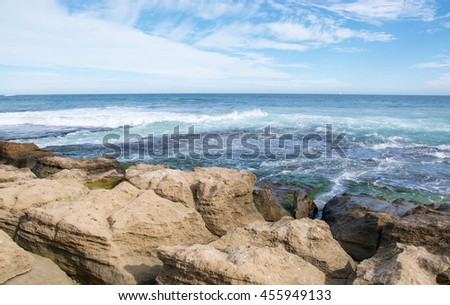 Limestone coast line at Penguin Island with rushing Indian Ocean waves under a blue sky with clouds  in Rockingham, Western Australia/Rushing Limestone/Penguin Island, Rockingham, Western Australia - stock photo