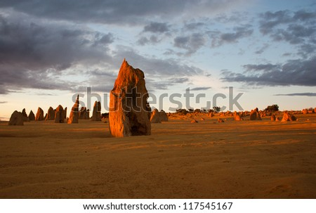 Limestone formations glowing red at last light in the Pinnacles desert in Nambung National Park, Western Australia - stock photo