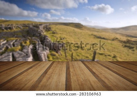Limestone rocks and flint walls lead towards Malham Moor in distance in Yorkshire Dales National Park with wooden planks floor - stock photo