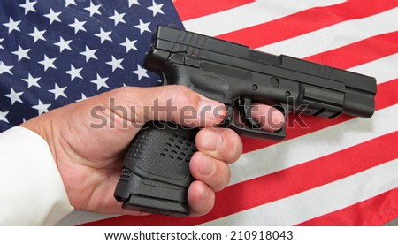 Limp man's hand holding automatic pistol against US flag. - stock photo