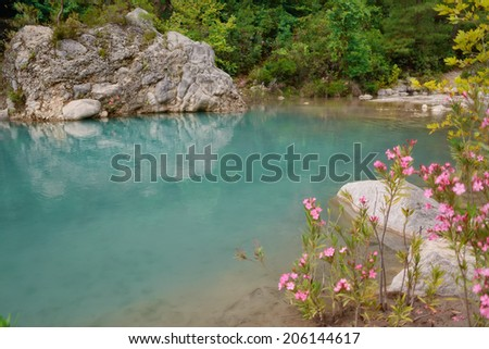 limpid lake beside the road on the background of green mountains - stock photo