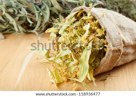 linden flowers in canvas bag on wooden table, herbal medicine - stock photo