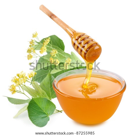 Linden honey is pouring with sticks in a jar. Next to them are linden flowers. Isolated on white background. - stock photo