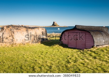 Lindisfarne Boats and Castle / Upturned boat hulls used for storage sheds on Holy Island, with Lindisfarne Castle behind - stock photo