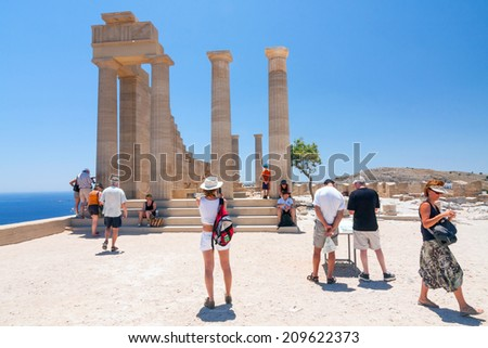 LINDOS, GREECE - JUNE 24: Unidentified tourists walking in historic town Lindos on June 24, 2008. Lindos is most popular turist destination located in the Rhodes Island, eastern Aegean Sea. - stock photo