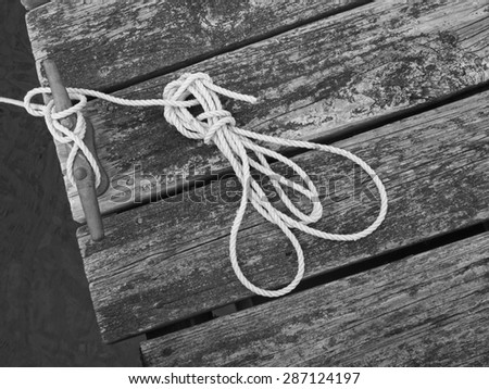 Line holding a moored skiff to the dock. - stock photo