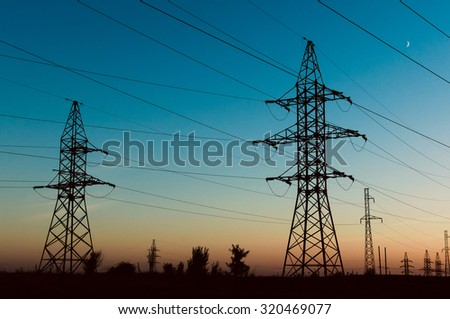 Line of an electricity transmission of a high voltage. High-voltage columns with wires before electric substation of the city. - stock photo