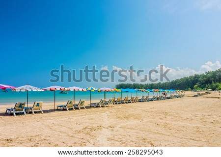 Line of beach umbrellas and sunbathing seats on Phuket sand beach in Southern Thailand - stock photo