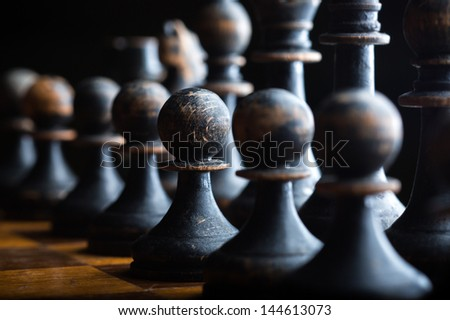 Line of black pawn chess pieces - stock photo