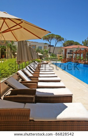 line of chaise lounges for tan by the pool - stock photo