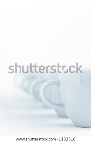 Line of cups on a white cloth - stock photo