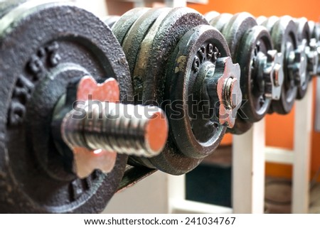 Line of dumbbells in the gym on orange background - stock photo