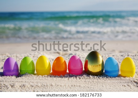 Line of easter eggs with gold egg on ocean beach  - stock photo