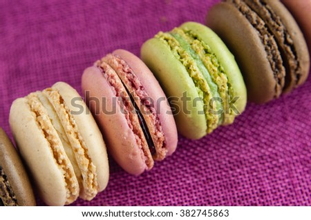 Line of macaroons on pink jute tablecloth closeup  - stock photo