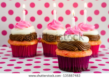 Line of 4 neapolitan frosted cupcakes sitting on pink polka dot background with lit birthday candles - stock photo