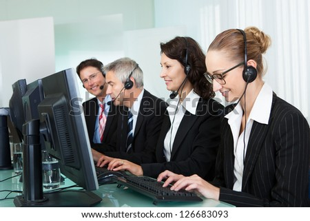 Line of professional stylish call centre operators wearing headsets seated behind their computers giving assistance - stock photo