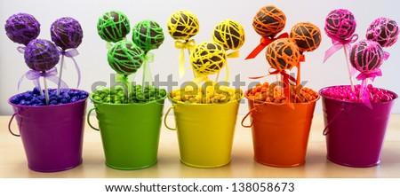 Line of rainbow colored chocolate cake pops in colored buckets and colored candy balls - stock photo