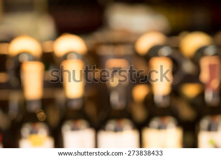 Line of wine bottles display in store, soft focus - stock photo