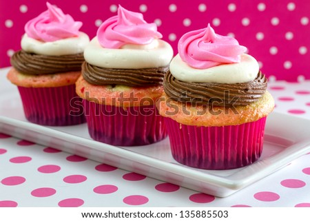 Line up of 3 neapolitan frosted cupcakes on white plate with pink polka dot table and background - stock photo