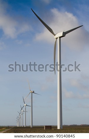 Line white wind turbine generating electricity in the Dutch polder - stock photo