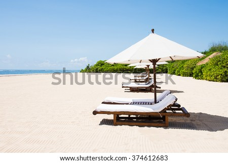lined beach chairs in front of beach - stock photo