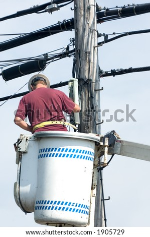 Lineman repairing a line after storm. - stock photo