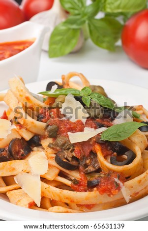 Linguine pasta with fresh tomato puttanesca sauce, cheese and basil - stock photo
