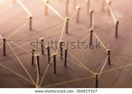 Linking entities. Network, networking, social media, connectivity, internet communication abstract. Web of thin gold wires on rustic wood. - stock photo