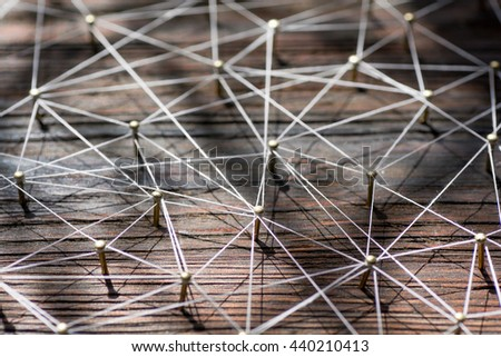 Linking entities. Network, networking, social media, internet communication abstract. A small  connected to  larger . Web of gold wires on rustic wood. - stock photo