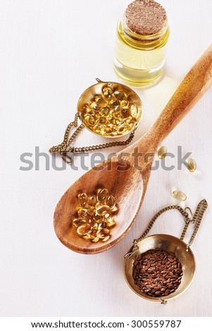 Linseed, flaxseed oil capsules and bottled flaxseed oil over white wooden background - stock photo