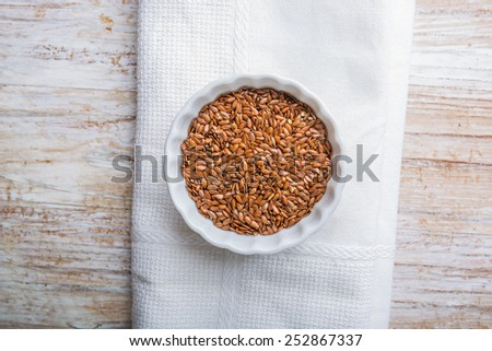 Linseed in white bowl - stock photo