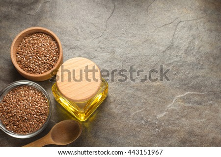 linseed oil in bottle and flax seeds on table background - stock photo