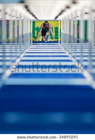 LINZ, AUSTRIA - AUGUST 2 Austrian track and field championship: Roland Schwarzl (#389) places second in the men's 110m hurdles event on August 2, 2009 in Linz, Austria. - stock photo