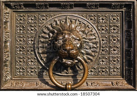 Lion head ornament on old cathedral door. - stock photo