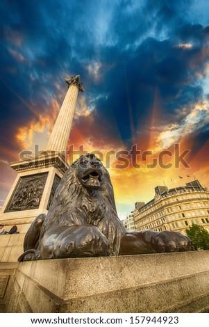 Lion Statue and Nelson Column at Trafalgar Square - Upward view at sunset, London, UK. - stock photo