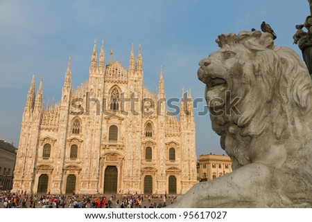 Lion statue in the Piazza del Duomo with cathedral at sunset  Milan, Italy - stock photo