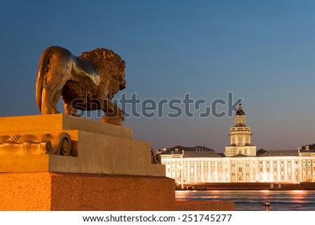 Lion statue looking at Kunstkamera across Neva - stock photo