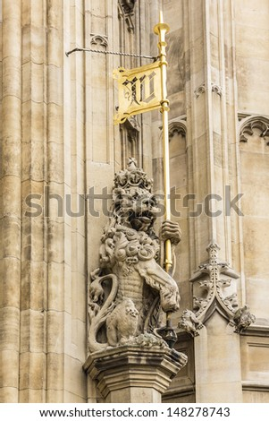 Lions at the entrance to Victoria Tower - largest and tallest (98 m) tower of Palace of Westminster. Palace of Westminster (or Houses of Parliament) located in City of Westminster, London. - stock photo