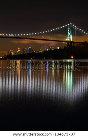 Lions Gate Night, Vancouver. Twilight in Vancouver with the Lion's Gate Bridge crossing to Stanley park and reflecting in Burrard Inlet. The office towers of downtown Vancouver in the back ground. - stock photo