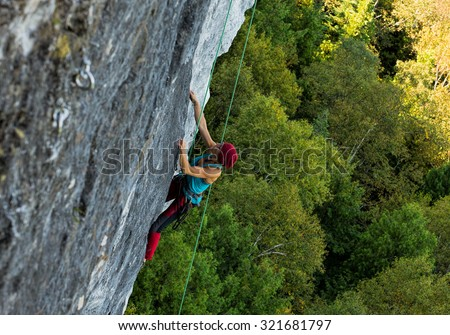 LIONS HEAD, ONTARIO - SEPT 26: Female climber scaling a steep limestone cliff at Lions Head in Ontario on September 26, 2015  - stock photo