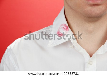Lipstick kiss on shirt collar of man, on red background - stock photo