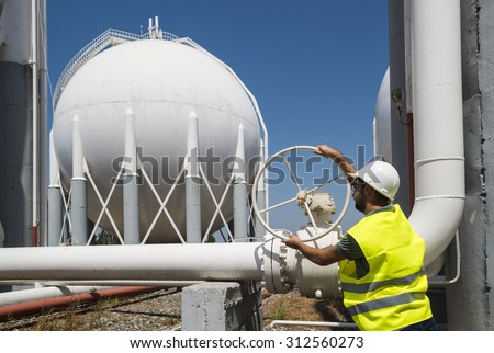 Liquefied Petroleum Gas tanks and Petrochemical Engineer. Engineers opens the gas valve - stock photo