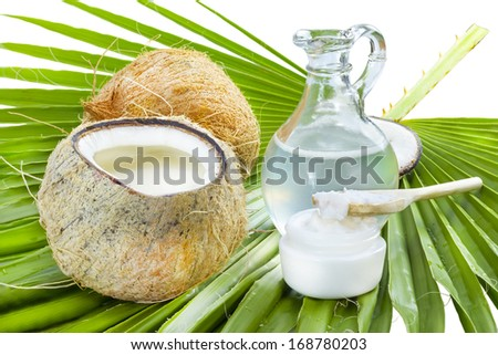 Liquid and solid coconut oil on palm leaf . - stock photo