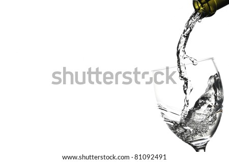 Liquid being poured into wine glass from bottle in a white background - stock photo