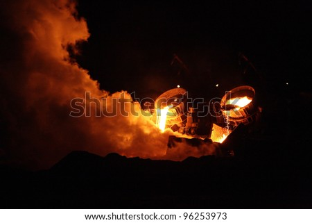 Liquid metal from a furnace with smoke - stock photo