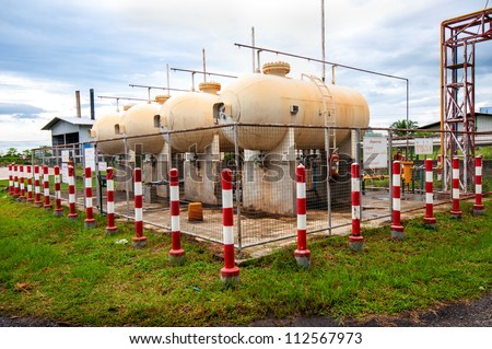 Liquid Petroleum Gas (LPG) storage unit inside a fence to prevent dangerous unauthorized intervention. Concept of Oil and Gas safety pre-caution measure. - stock photo