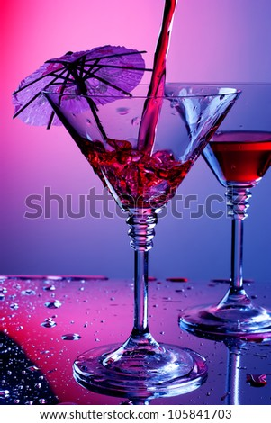 Liquid pouring into martini glass - stock photo