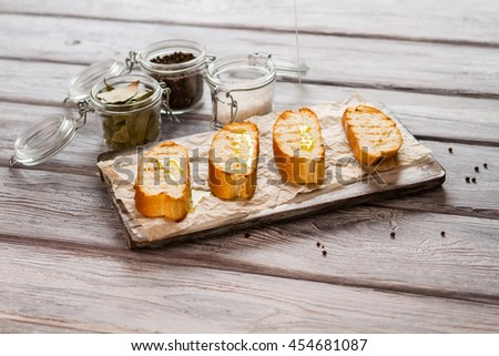 Liquid pours on baguette slice. Jar with whole pepper. How to prepare italian snack. Grilled bread and olive oil. - stock photo